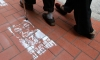 People in Hong Kong walk past street stencils of detained Chinese artist and activist Ai Weiwei. The words 'Who's afraid of Ai Weiwei' are painted underneath.