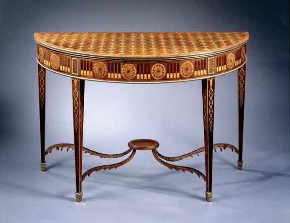 A rare and extraordinary pair of George III marquetry tables attributed to John Linnell, each with crossbanded marquetry tops centred with flowerheads, each frieze with gilt metal borders and trompe l'oeil flutes and paterai, on square tapered legs with entwined marquetry headed by husks, on ormolu stopped spade feet. Circa 1780, H. 33½, D. 20½, W. 51½ inches. Courtesy  of Clinton Howell Antiques.