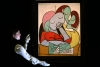 """An employee poses with artist Pablo Picasso's """"Femme Lisant (Deux Personnages)"""" at Sotheby's. The piece was expected to reach up to $ 35 million."""